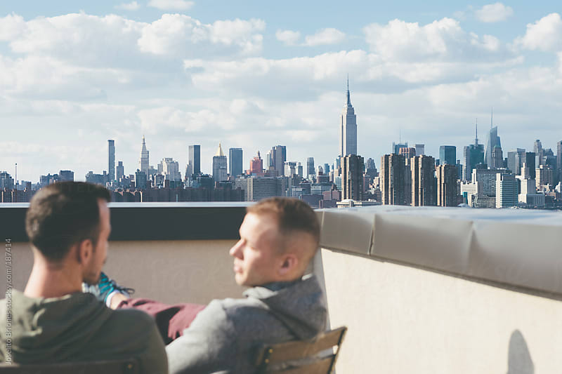 Gay Men Friends Hanging Out on a Rooftop Enjoying the View in New York by Joselito Briones for Stocksy United
