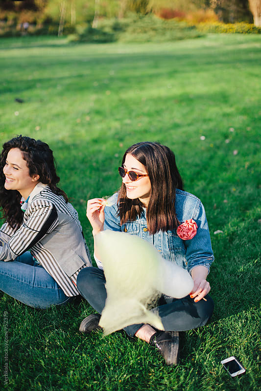 Two female friends having a great time in a park  by Marija Mandic for Stocksy United