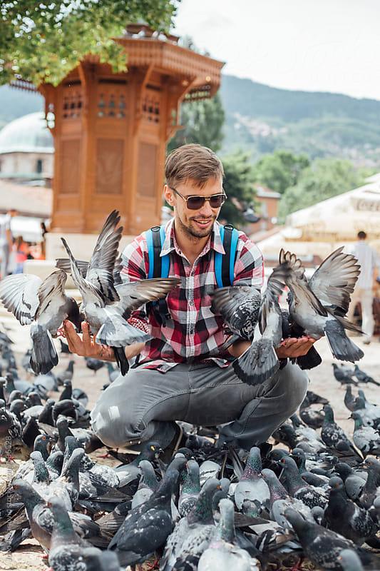 Man feeding pigeons in Sarajevo by Jovo Jovanovic for Stocksy United