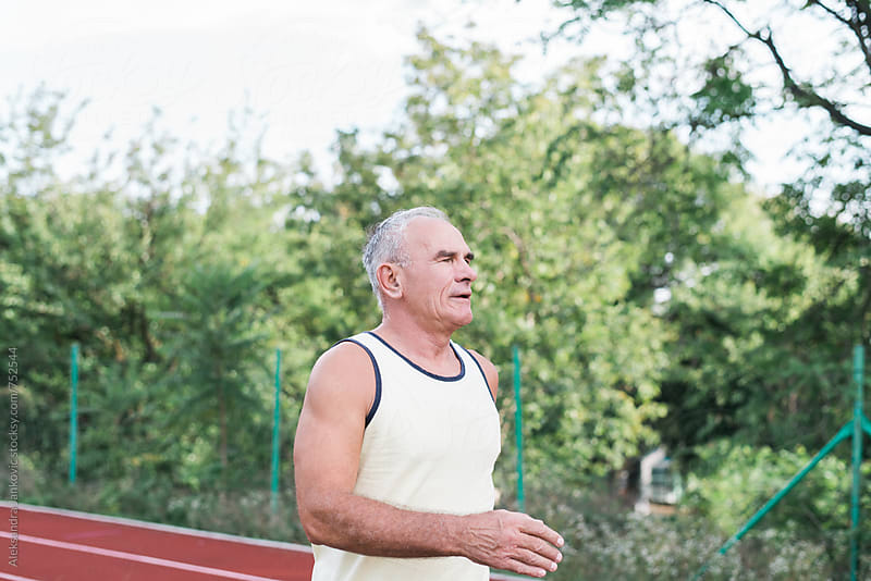 Middle-aged Man Jogging  by Aleksandra Jankovic for Stocksy United