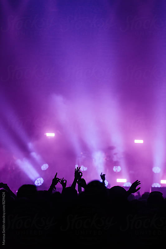 Purple and blue stage lights above a crowd of hands in the air gesturing 'ok' by Maresa Smith for Stocksy United