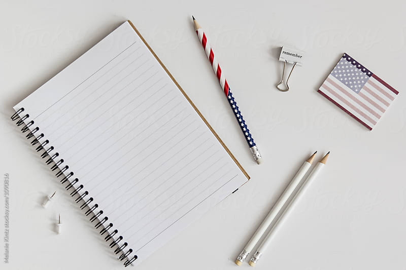 Open blank notebook, stars and stripes pencil and other office utensils by Melanie Kintz for Stocksy United