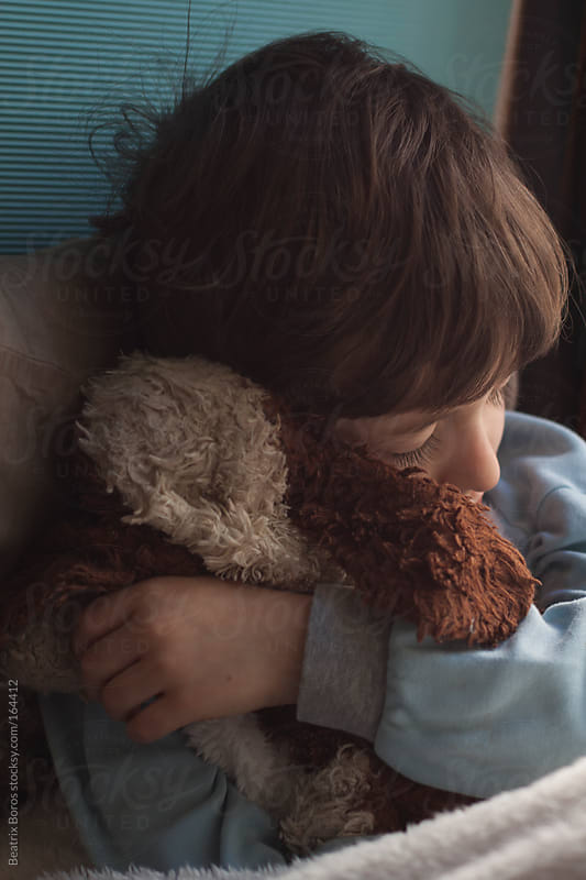 Little boy taking a nap hugging his furry toy puppy by Beatrix Boros for Stocksy United
