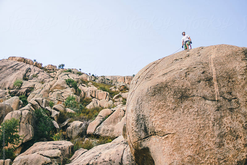 Climber on top of a rock after climbing it by Alejandro Moreno de Carlos for Stocksy United