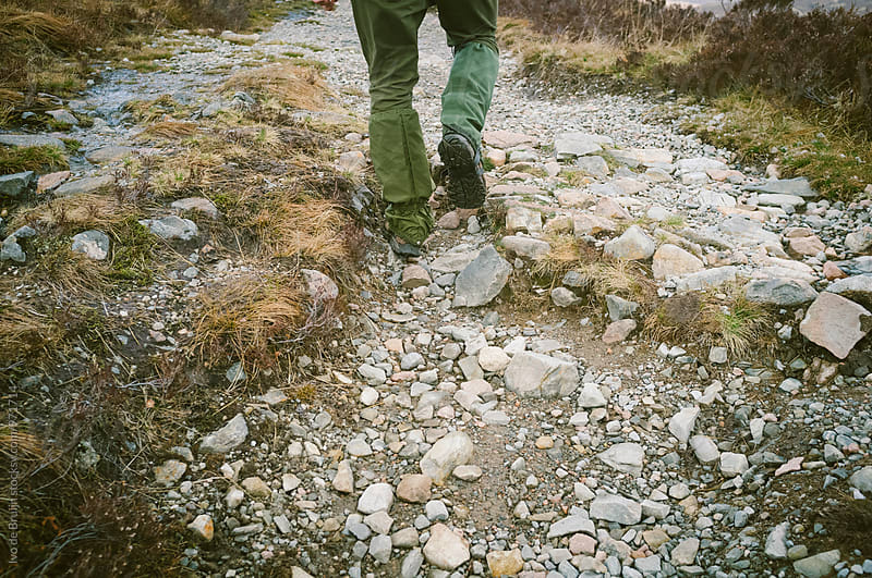 Close up of someone's boots and legs, walking on a rugged path with stones by Ivo de Bruijn for Stocksy United