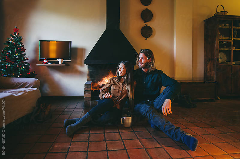 Smiling couple sitting by the fireplace on Christmastime. by BONNINSTUDIO for Stocksy United