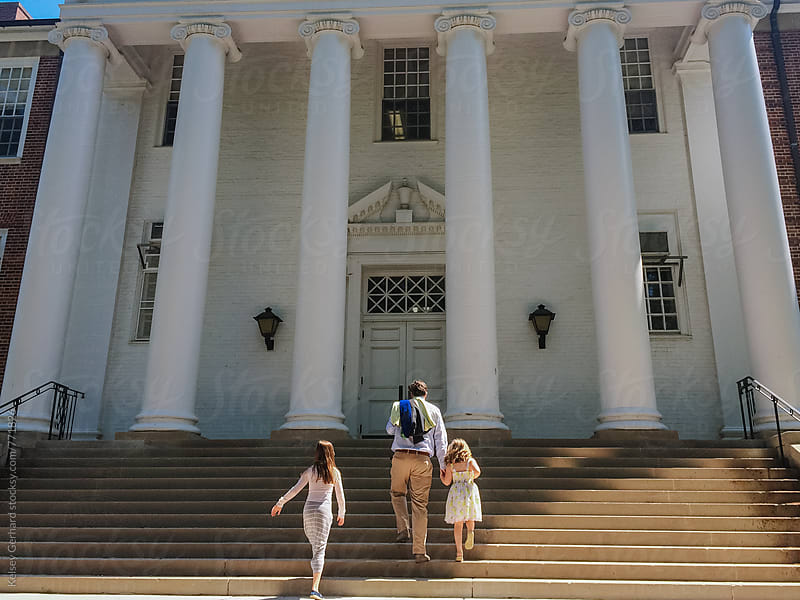 A father walks with his daughters up the steps at a University. by Kelsey Gerhard for Stocksy United