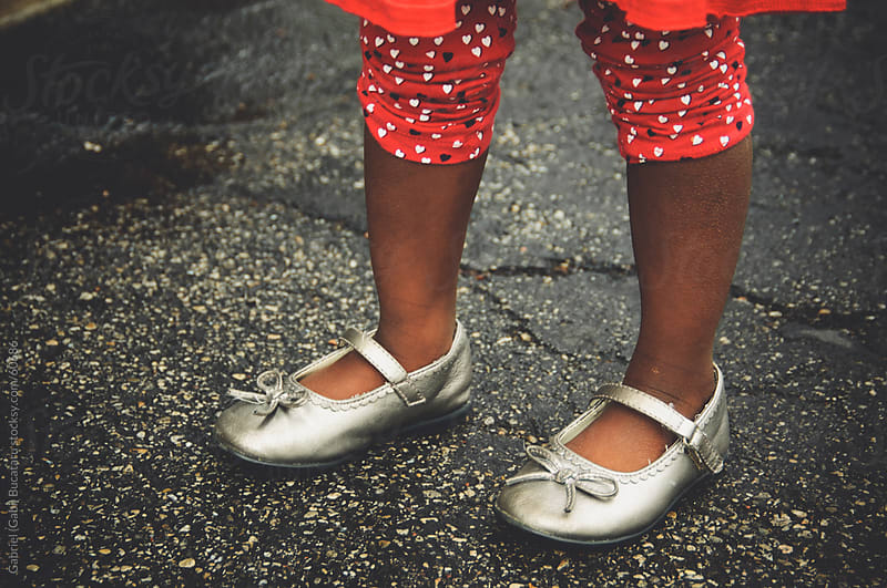 African American girl's feet wearing silver shinning shoes by Gabriel (Gabi) Bucataru for Stocksy United