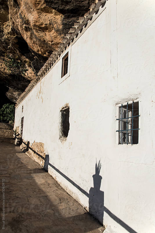 White fcade of a house cave on a rock in Montefrio, Andalusia, Spain by Bisual Studio for Stocksy United
