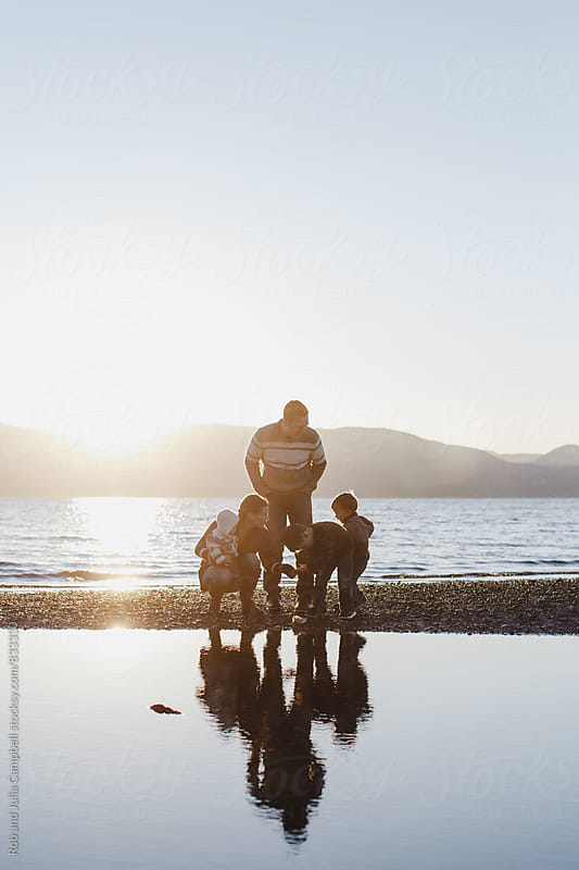 Young family of five enjoying the ocean beach at sunset by Rob and Julia Campbell for Stocksy United