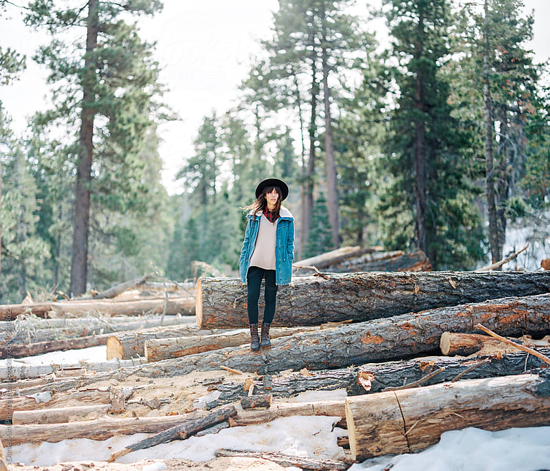 Girl standing on tree logs by Daniel Kim Photography for Stocksy United