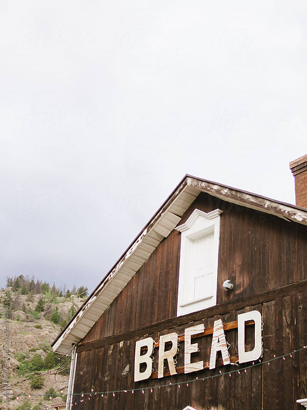 Old store with bread sign in mountain ghost town by Jeremy Pawlowski for Stocksy United