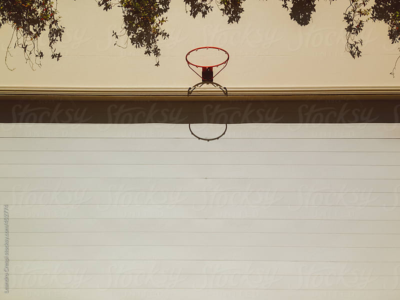 Basketball ring in front of a house by Leandro Crespi for Stocksy United