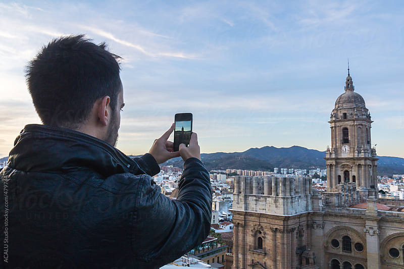 Young man photographing Malaga Cathedral with her mobile phone by ACALU Studio for Stocksy United