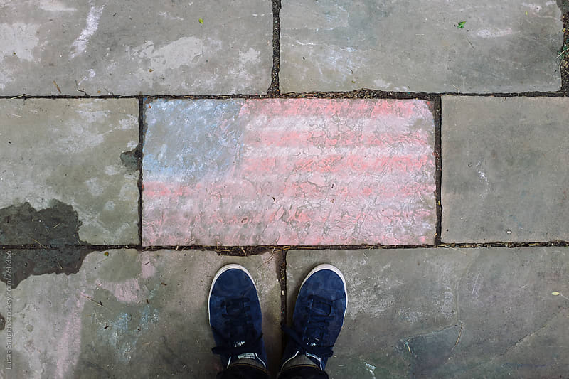 Looking down at my feet and a hand drawn american flag that has been rained on and since dried. by Lucas Saugen for Stocksy United