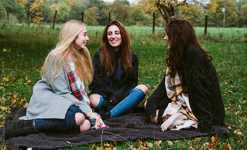 3 teenage girls hanging out together outdoors by Helen Rushbrook for Stocksy United