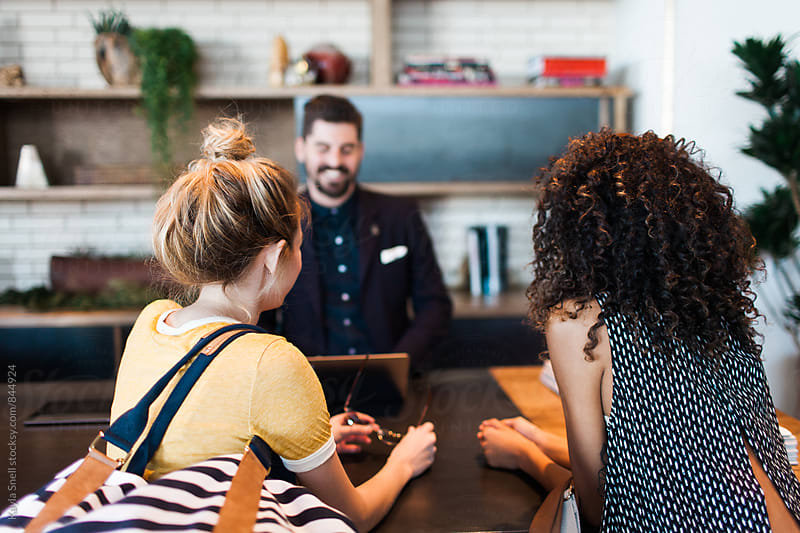Young women checking into hotel by Kayla Snell for Stocksy United