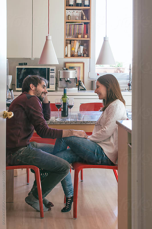 Portrait of young couple drinking wine on the kitchen.  by BONNINSTUDIO for Stocksy United