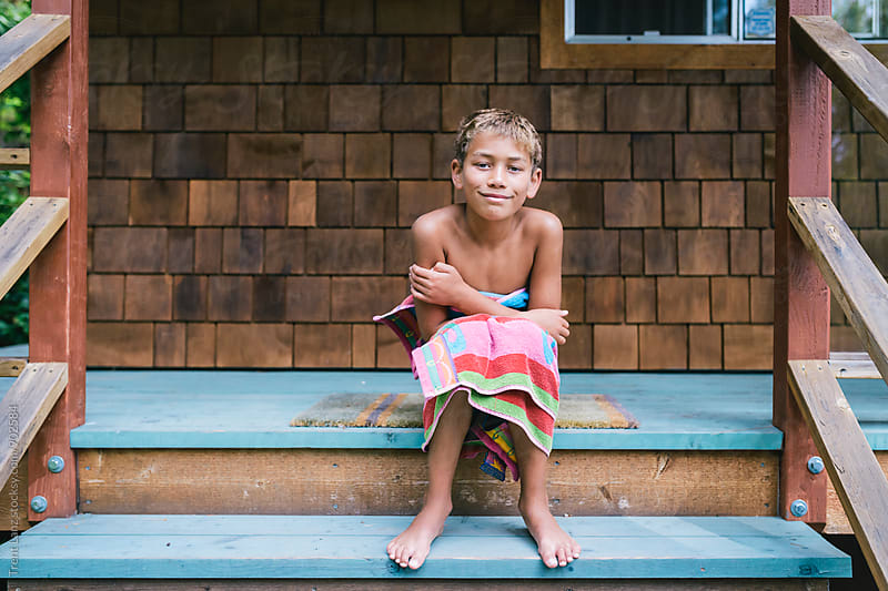 Barefoot boy sitting on steps in towel by Trent Lanz for Stocksy United