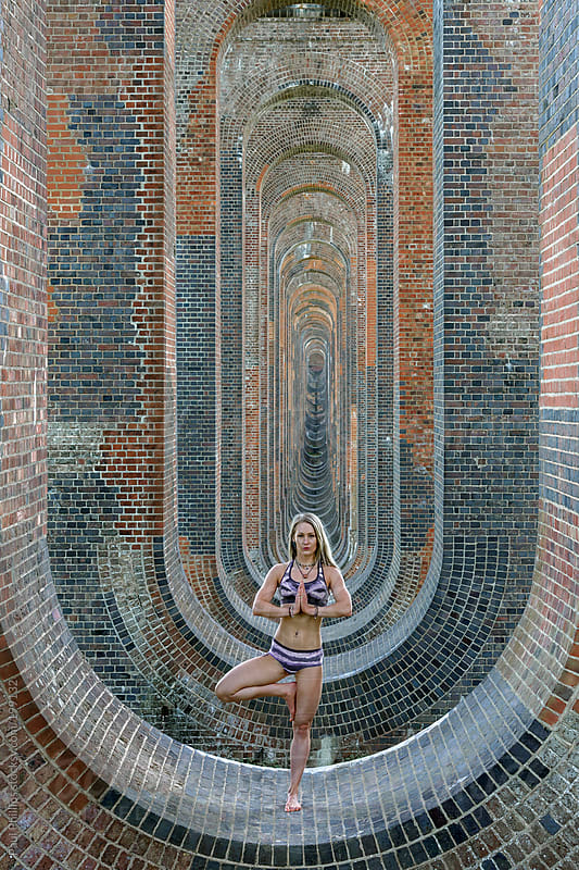 20s girl performing a yoga tree pose inside railway viaduct arches by Paul Phillips for Stocksy United