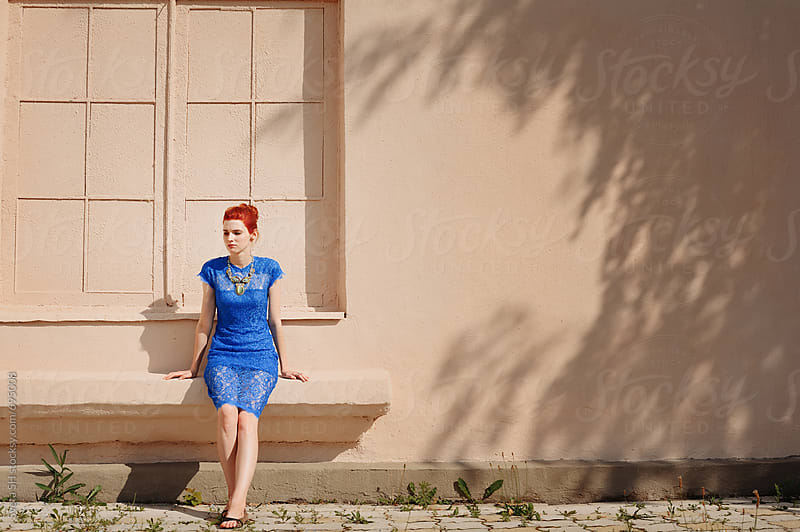 Red-haired girl in a blue dress  by Sveta SH for Stocksy United
