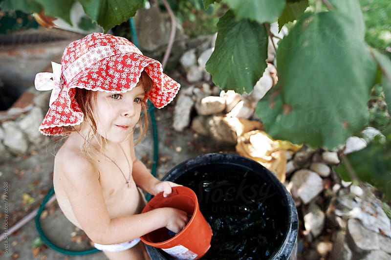 Little girl in red panama hat near the water barrels by Svetlana Shchemeleva for Stocksy United