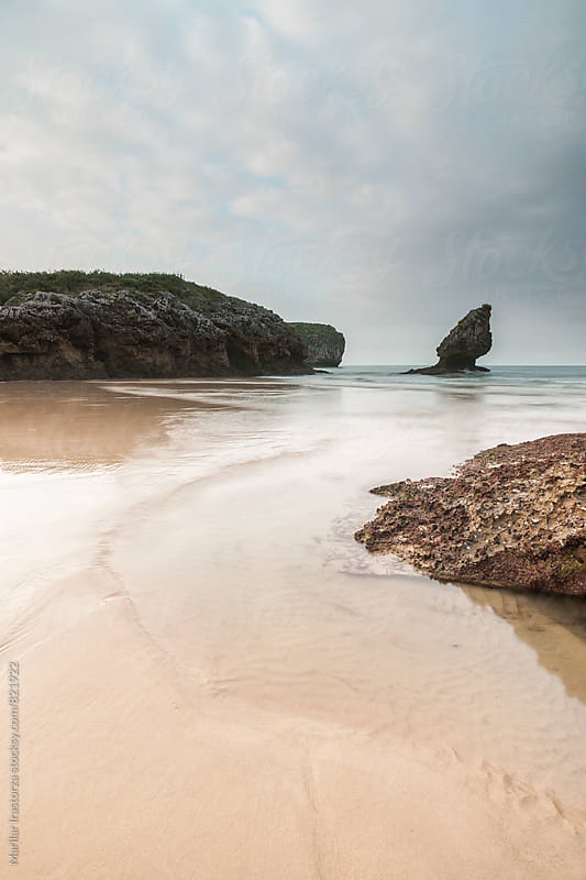 Beautiful beach at low tide on a cloudy day by Marilar Irastorza for Stocksy United