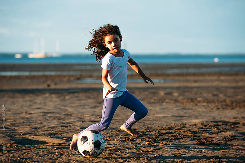 Girl plays soccer on beach. by Shannon Aston for Stocksy United
