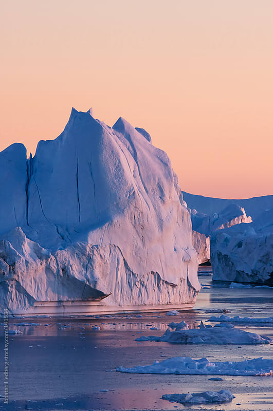 Icebergs in the sunset by Jonatan Hedberg for Stocksy United