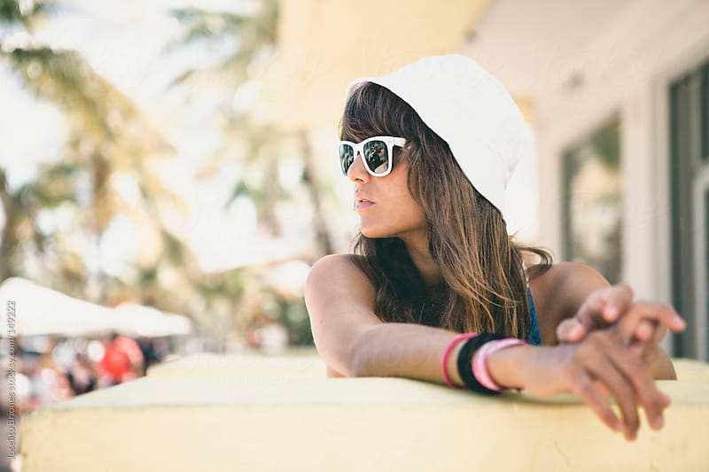 Young Woman with Hat and Glasses Spring Break in Miami by Joselito Briones for Stocksy United