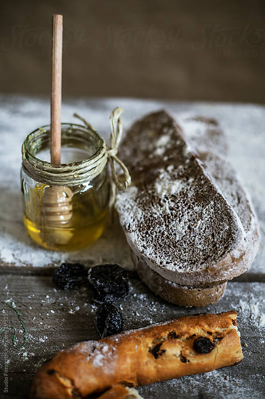 Bread and honey on the table by Studio Firma for Stocksy United