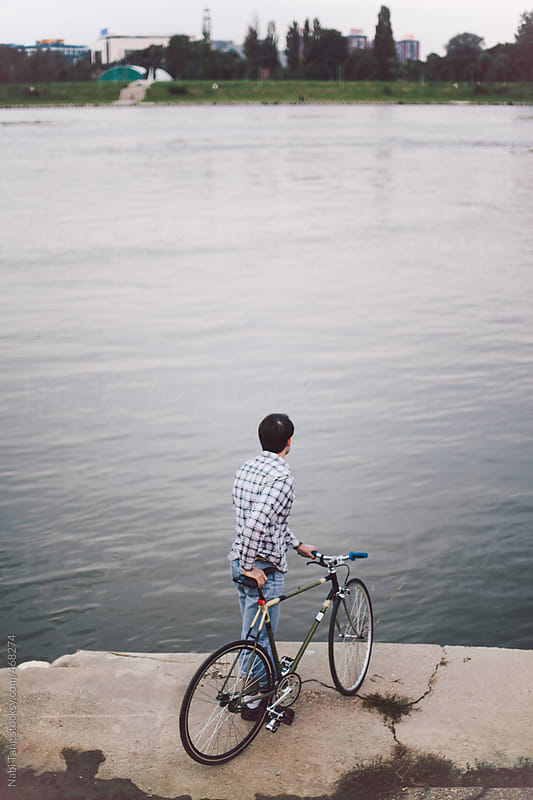 Young man with a bicycle looking over the other side of the river by Nabi Tang for Stocksy United
