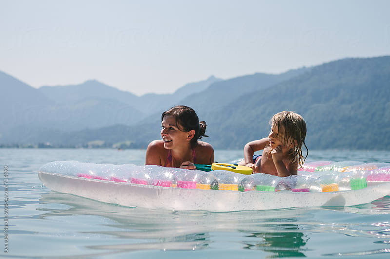 mother and son relaxing on an air mattress on a beautiful lake by Leander Nardin for Stocksy United