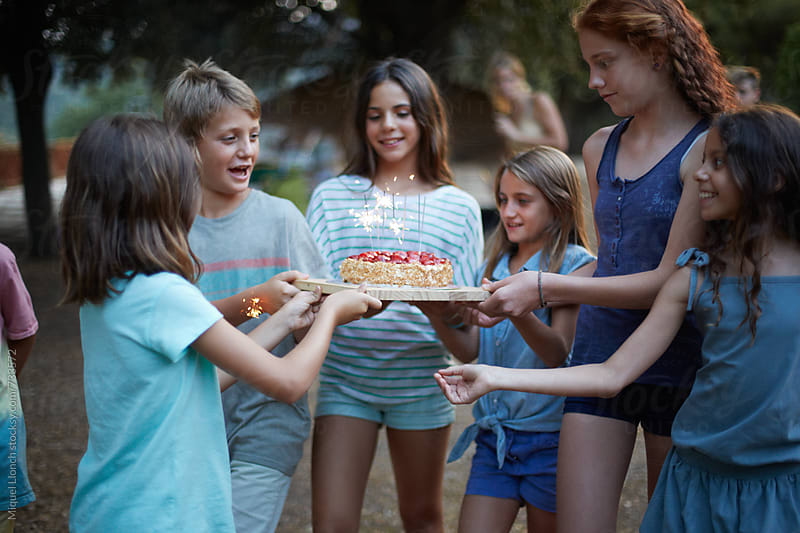 Group of children carefully carrying a birthday cake with sparkles by Miquel Llonch for Stocksy United