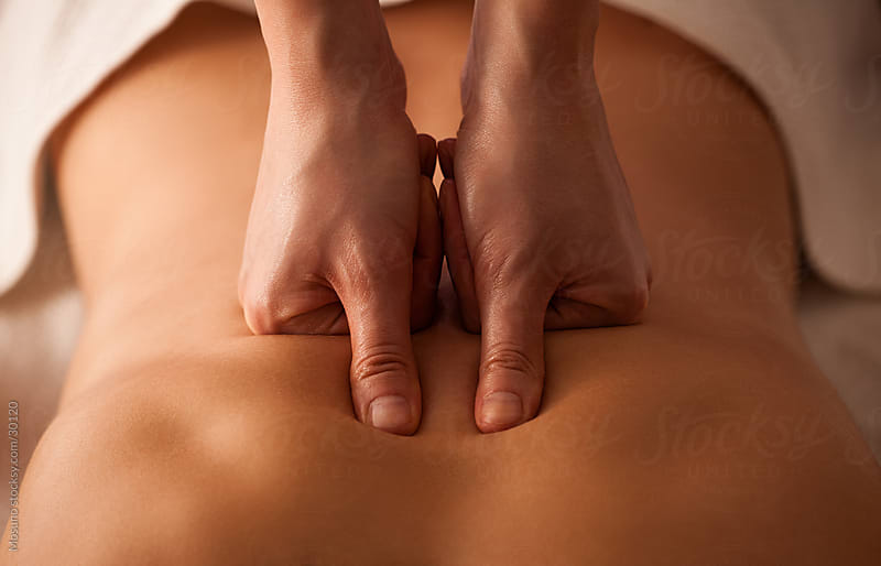 Close up of a masseuse's hands massaging female back. by Mosuno for Stocksy United