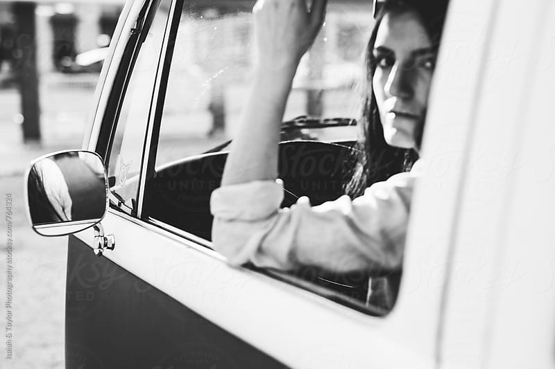 Young woman sitting in an old car by Isaiah & Taylor Photography for Stocksy United