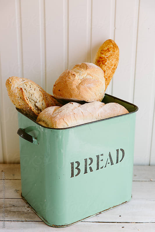 Various types of bread in a vintage bread bin. by Helen Rushbrook for Stocksy United