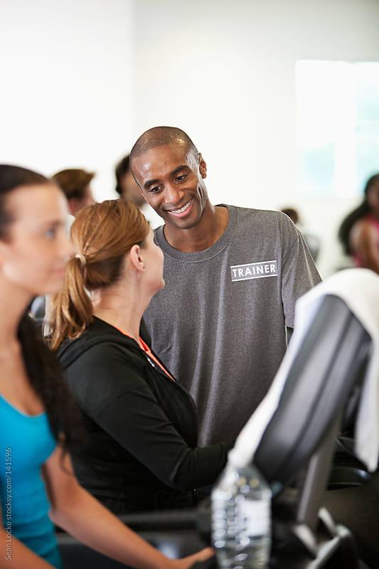 Gym: Trainer Helps Woman With Treadmill by Sean Locke for Stocksy United