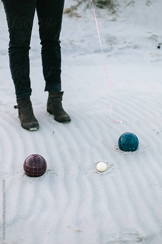 Two different bocce game balls in sand with measuring tape by Matthew Spaulding for Stocksy United