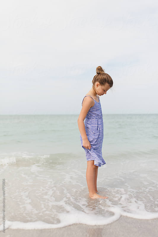 Profile of a preteen girl looking into the ocean with a soft smile  by Amanda Worrall for Stocksy United
