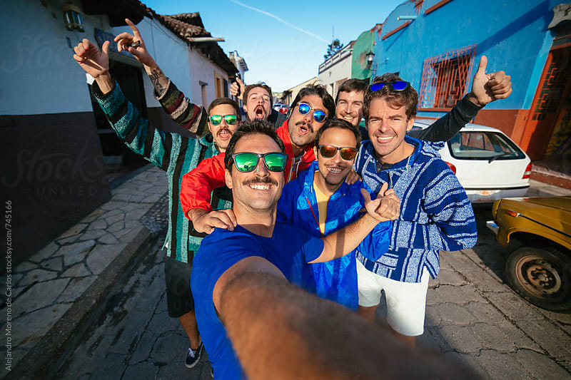 Group of happy friends taking a selfie in a colourful street on their vacation trip by Alejandro Moreno de Carlos for Stocksy United