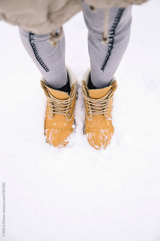 Woman's feet in boots standing in snowdrift. Unrecognizable by T-REX & Flower for Stocksy United