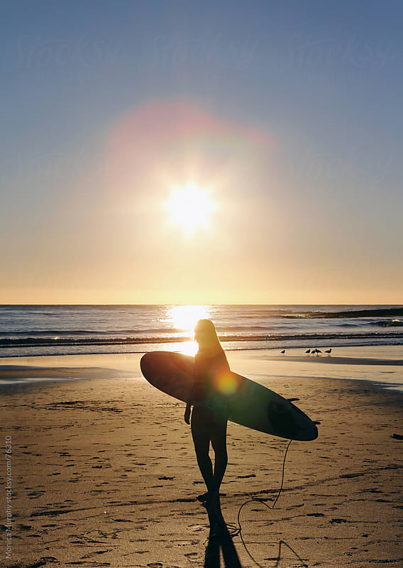 Girl walking beach carrying surf board at sunset by Monica Murphy for Stocksy United