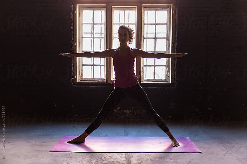 Woman doing warrior yoga pose in a studio by Jovo Jovanovic for Stocksy United