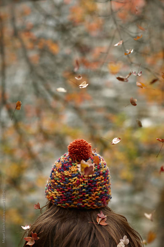 Young girl with hat and fall leaves  by Miquel Llonch for Stocksy United