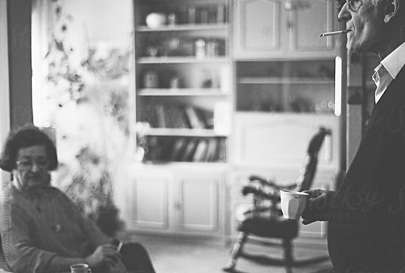 Old couple drinking coffee and smoking at home by Marija Anicic for Stocksy United