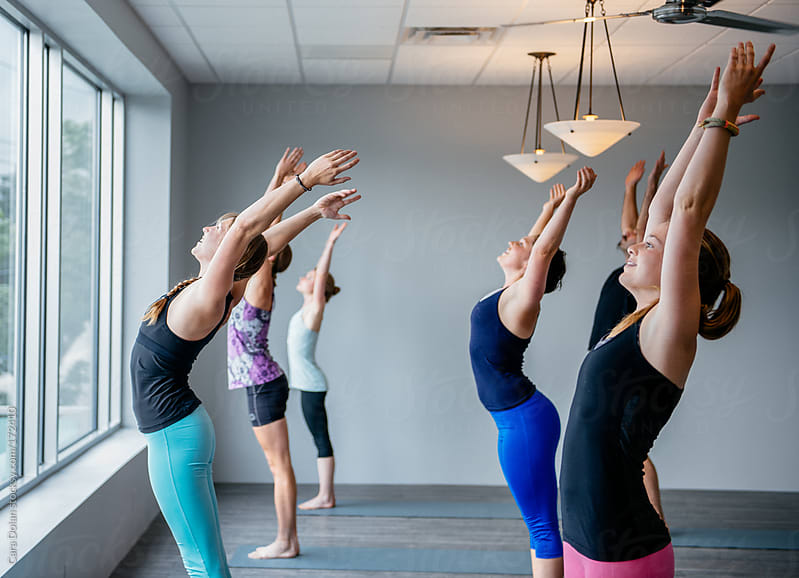 Students in a beginner yoga class  by Cara Dolan for Stocksy United