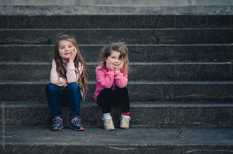 Cute Sisters Sitting On Steps by Leslie Taylor for Stocksy United