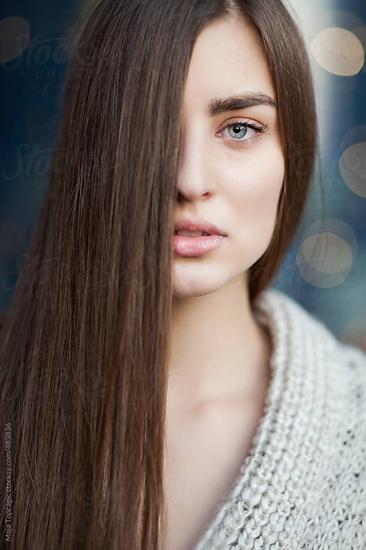 Young beautiful woman with blue eyes and long brown hair covering half face by Maja Topcagic for Stocksy United