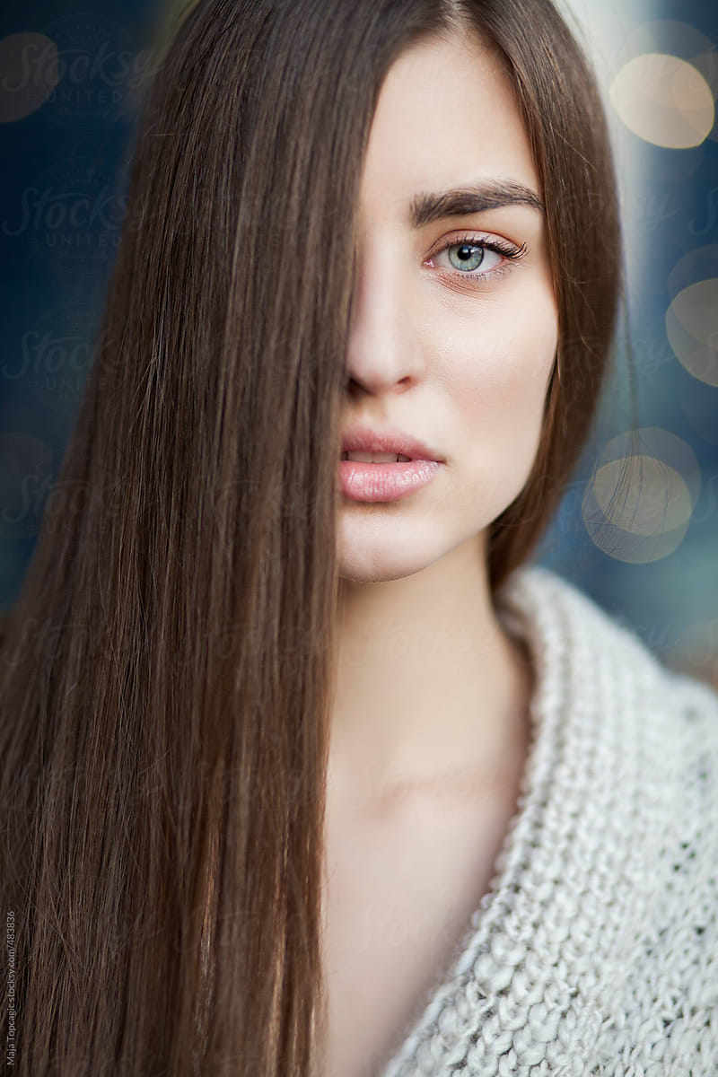 Young Beautiful Woman With Blue Eyes And Long Brown Hair Covering Half Face By Maja Topcagic Stocksy United